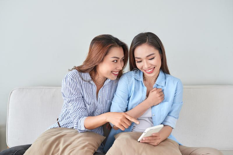 Close up portrait of two excited girlfriends with mobile phones, laughing. Happy joyful female friends resting at home, enjoying stock image
