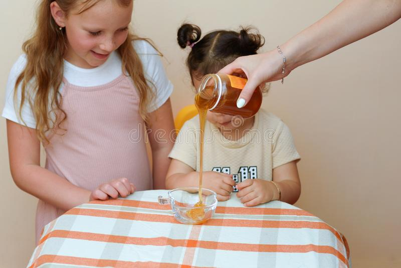 Close up portrait of two funny cute little girl looking on woman hand pouring fresh honey from jar into bowl. royalty free stock photos