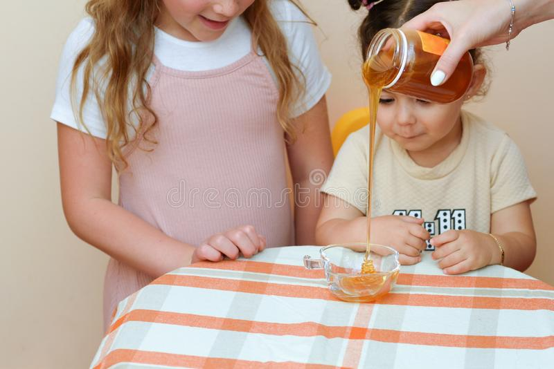 Close up portrait of two funny cute little girl looking on woman hand pouring fresh honey from jar into bowl. stock images