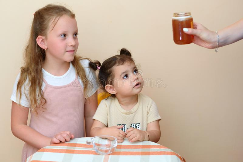 Close up portrait of two funny cute little girl looking on mom hand holding fresh honey. stock photo