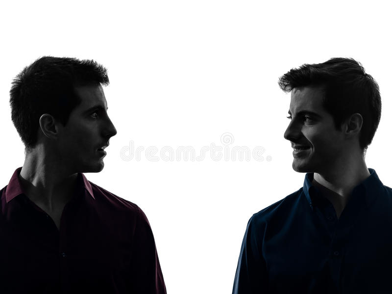 Close up portrait two men twin brother friends silhouette. Close up portrait two caucasian young men in shadow white background stock images