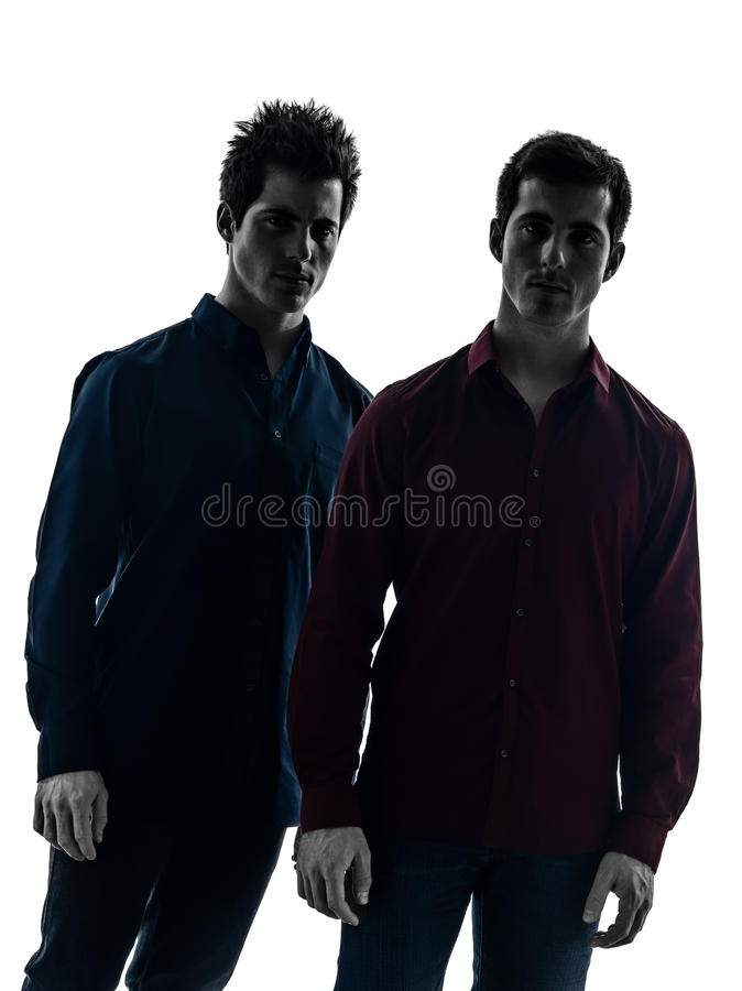 Close up portrait two men twin brother friends silhouette. Close up portrait two caucasian young men in shadow white background royalty free stock image