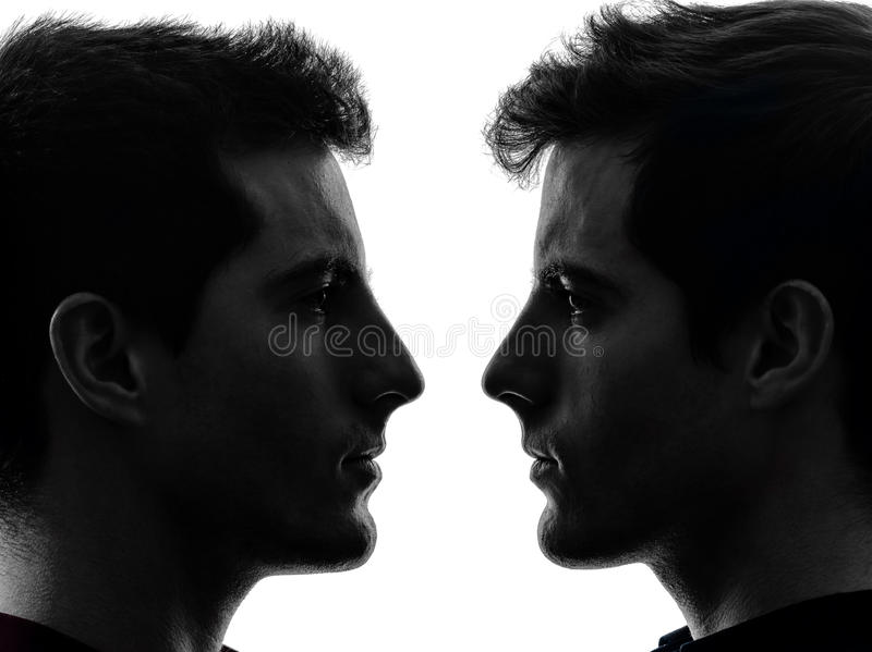 Close up portrait two men twin brother friends silhouette. Close up portrait two young men in shadow white background royalty free stock images