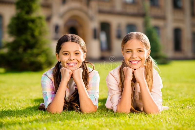 Close-up portrait of two nice attractive charming lovely cute cheerful cheery pre-teen girls lying in green grass fresh stock photography