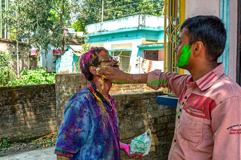 Close up portrait of two young man are coloring each other during the Holi festival in India royalty free stock image