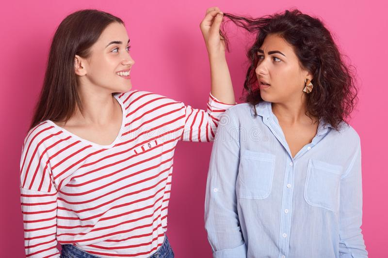 Close up portrait of two young women, girl wearing striped shirt touches friends hair with fingers, attractive lady looks at royalty free stock images