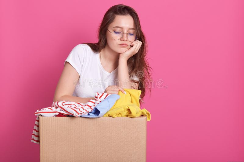 Close up portrait of unhappy young woman posing with box of clothes donation, has sad facial expression, looking down, keeps hand royalty free stock photos