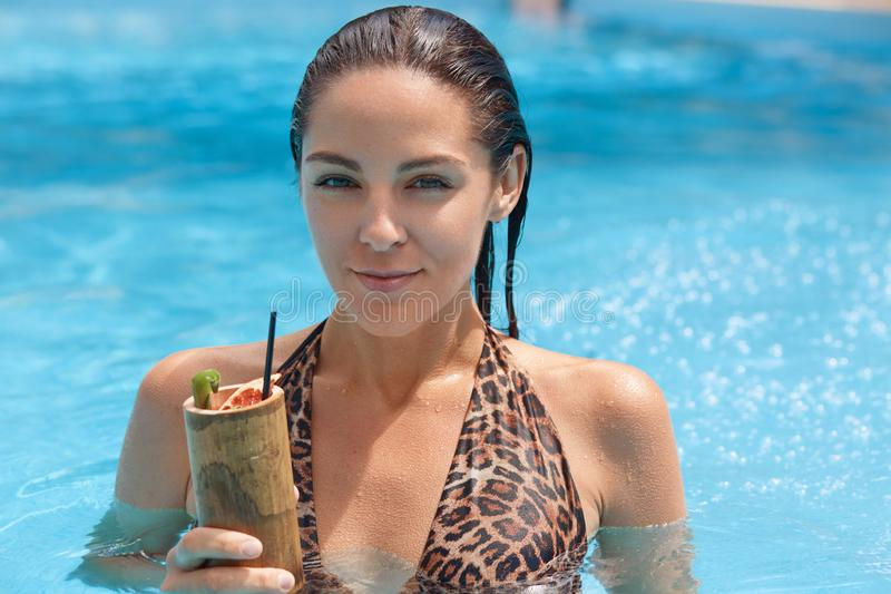 Close up portrait of wet European brunette young lady standing in swimming pool, looking directly at camera, holding cocktail in stock images