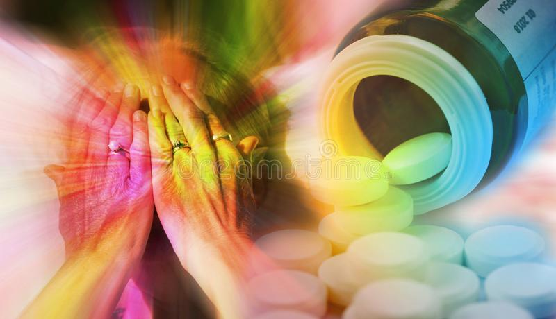 Close up portrait of woman covering her face with hands and pills pouring out from a pill bottle. Drug addiction, medicine a stock photography