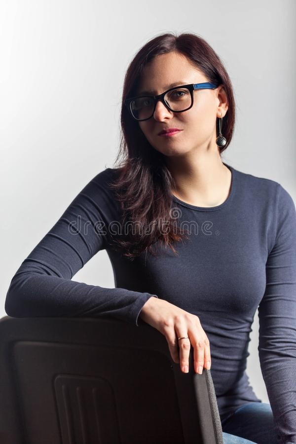 Close up portrait of woman in glasses posing on chair stock images