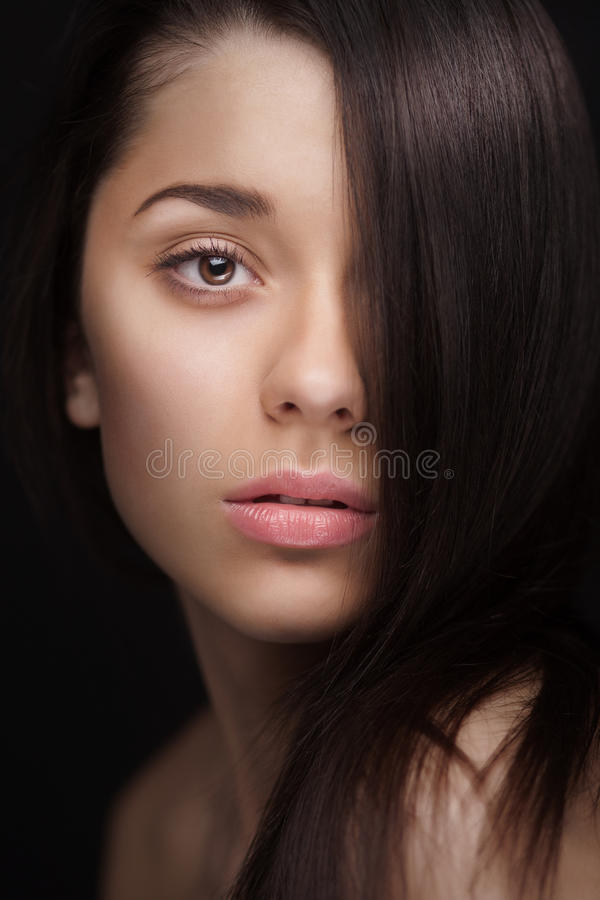 Close up of a woman with hair over half her face. Close up portrait of a woman with hair over half her face stock photography
