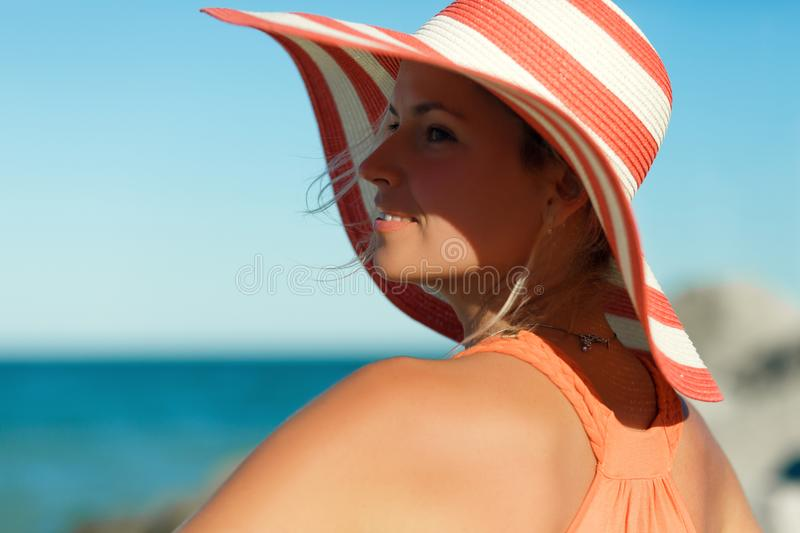 Close up portrait of Woman in orange dress on sea beach. Close up portrait of Woman in orange dress and hat on sea beach stock images