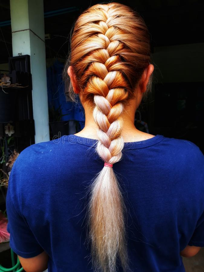 Close-up portrait of a woman& x27;s back, braid, beautiful hair, golden hair, fashion, braiding with professional hairdressers royalty free stock photography