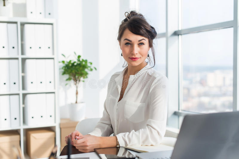 Close-up portrait of a woman sitting in modern loft office, smiling, looking at camera. Young confident female business royalty free stock images