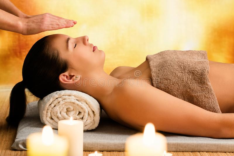 Young woman relaxing in spa at reiki session. royalty free stock photo
