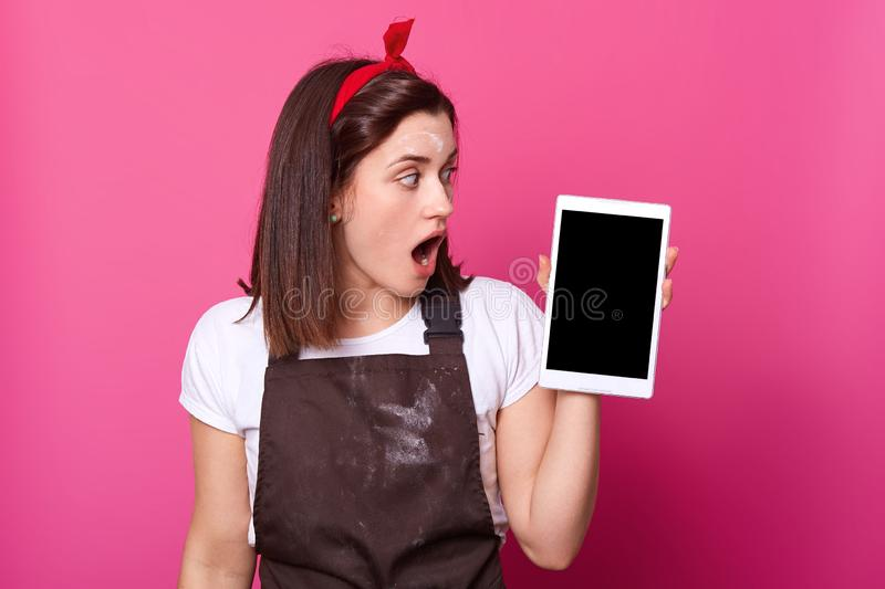 Close up portrait of woman stands over pink background, holds smart phone, looks aside on her gadget. Dark haired astonished stock photography
