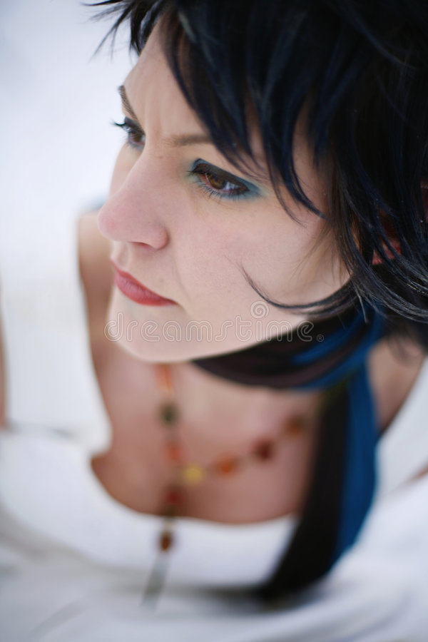 Close-up portrait of a woman wearing a stylish whi. A close-up portrait of a woman with dark hair wearing a stylish white dress and a black and blue scarf stock photos