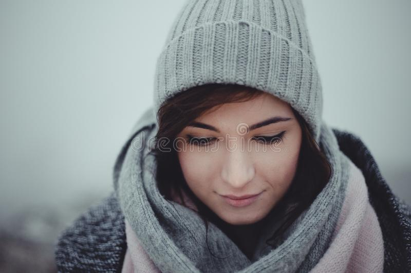 Close up portrait of woman who looking down on misty background. Photo of beautiful fashion model with a cap in winter time. Girl stock images