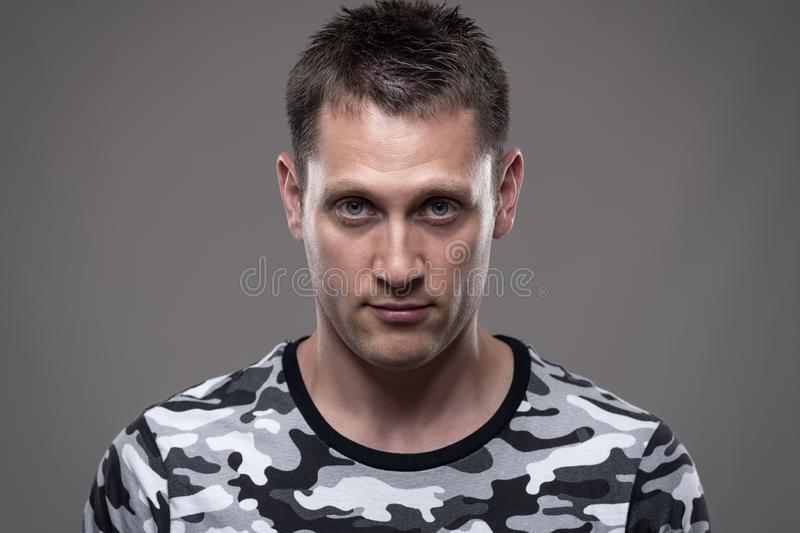 Close up portrait of young adult man in army shirt looking intense at camera at attention. Over gray studio background stock images