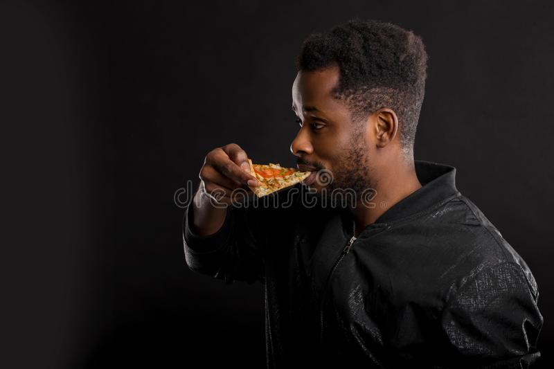 Close up portrait of young african man eating pizza royalty free stock image