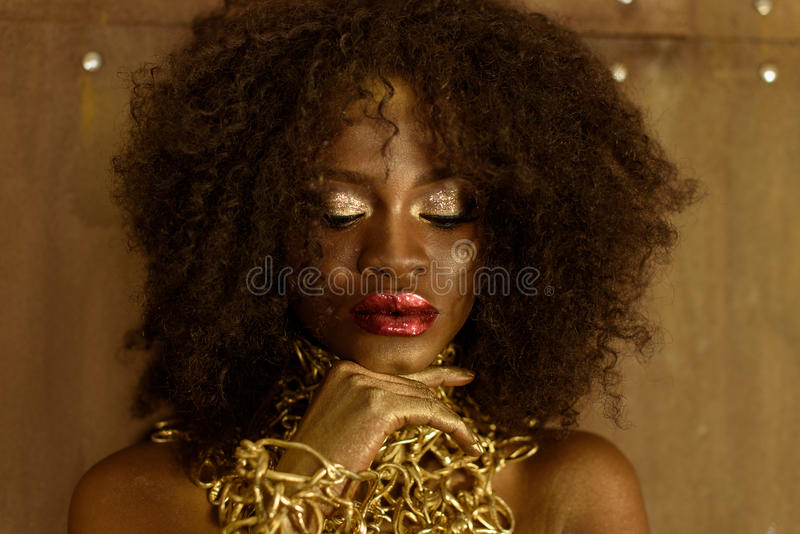 Close-up portrait of young African woman with gold makeup and necklace, laying hands on her chin looking down, brown background royalty free stock images