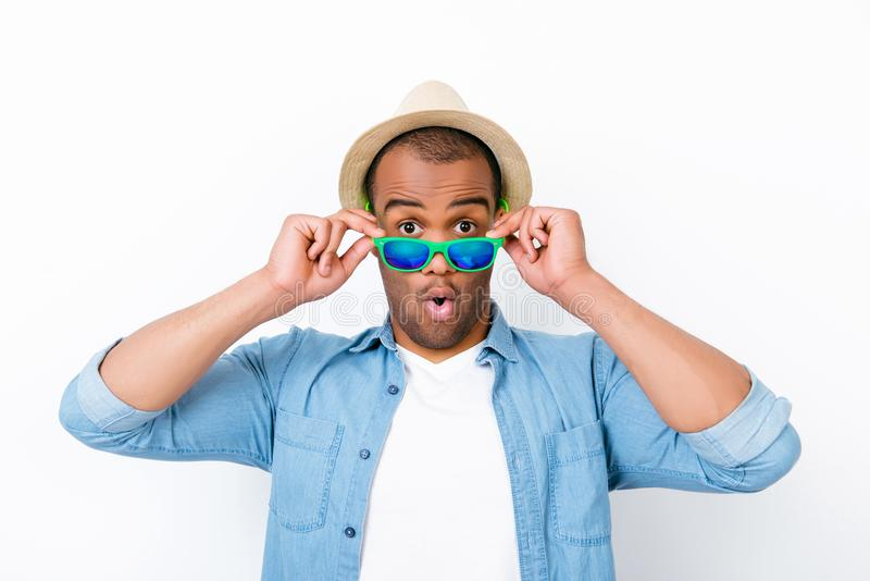 Close up portrait of young afro american shocked tourist , holding his eyewear, wearing tourist`s outfit, hat, with wide open eyes royalty free stock photos
