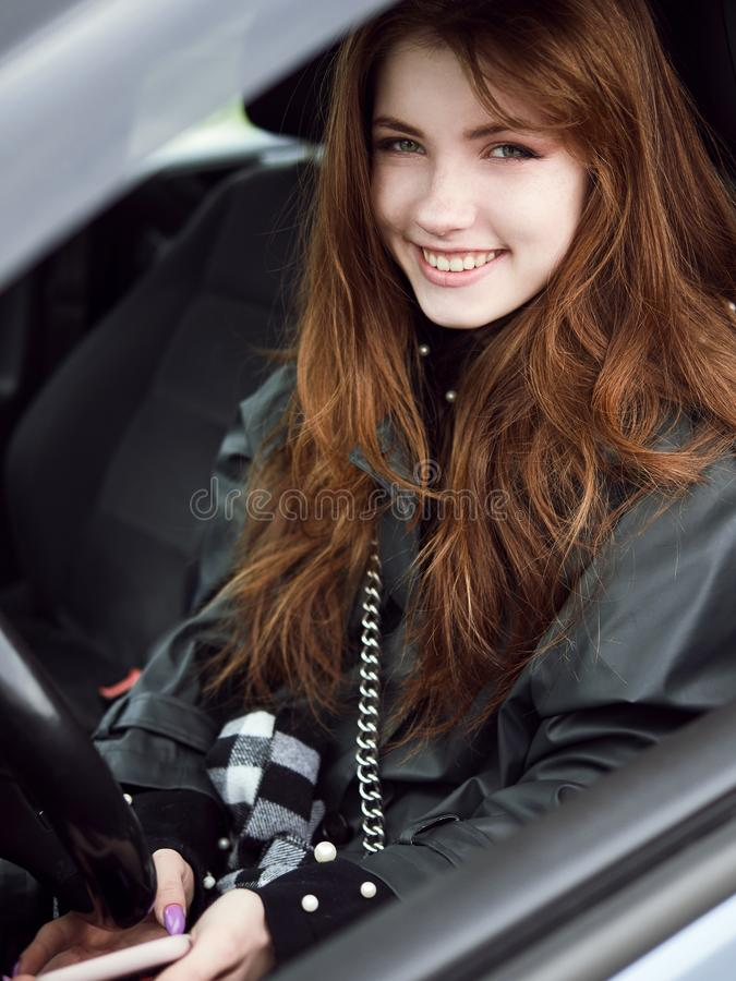 Close up portrait of young attractive red hair self-employed business woman driver sitting in white car stuck in a city traffic royalty free stock photos