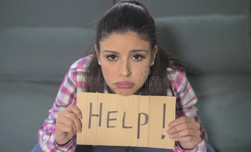 Close up portrait of young attractive and sad hispanic woman sitting at home couch looking stressed and worried showing help sign. Feeling helpless in domestic stock photography