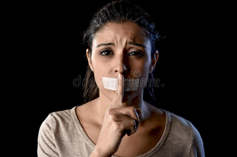 Close up portrait of young attractive woman with mouth and lips sealed in adhesive tape restrained. And abused censored and banned to speak and express opinion royalty free stock photography