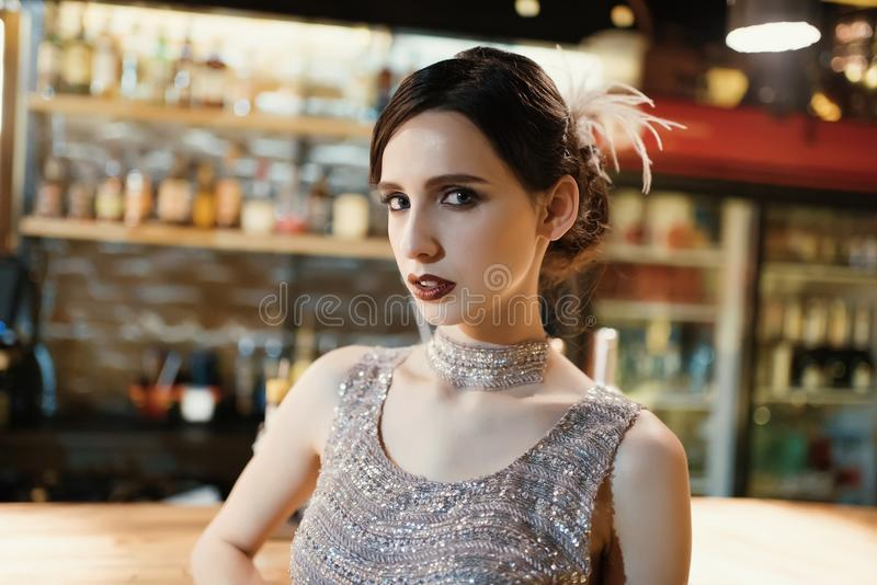 Close-up portrait of a young attractive woman in a 1920s style at the bar. Model with a beautiful make-up. In Bar royalty free stock photos