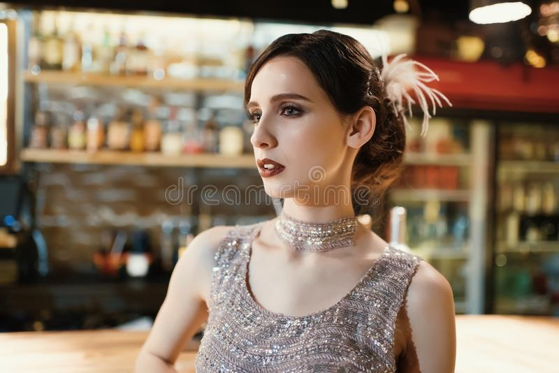 Close-up portrait of a young attractive woman in a 1920s style at the bar. Model with a beautiful make-up. In Bar stock photos