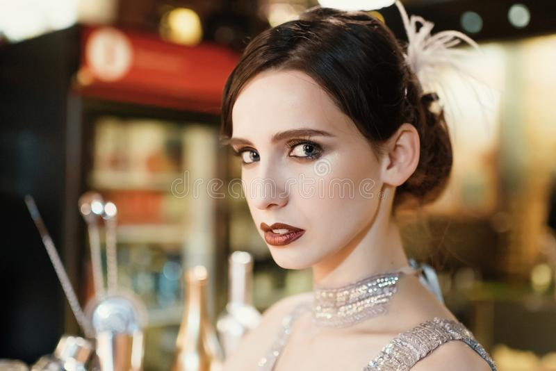 Close-up portrait of a young attractive woman in a 1920s style at the bar. Model with a beautiful make-up. In Bar royalty free stock photography