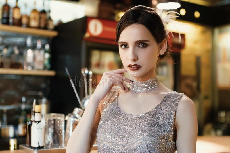 Close-up portrait of a young attractive woman in a 1920s style at the bar. Model with a beautiful make-up. In Bar royalty free stock images