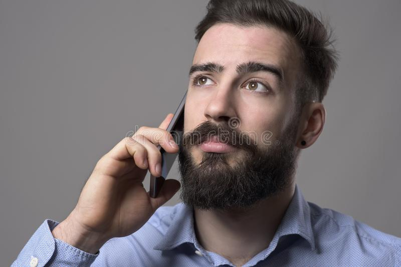 Close up portrait of young bearded business man talking on the mobile phone looking up at copyspace stock image