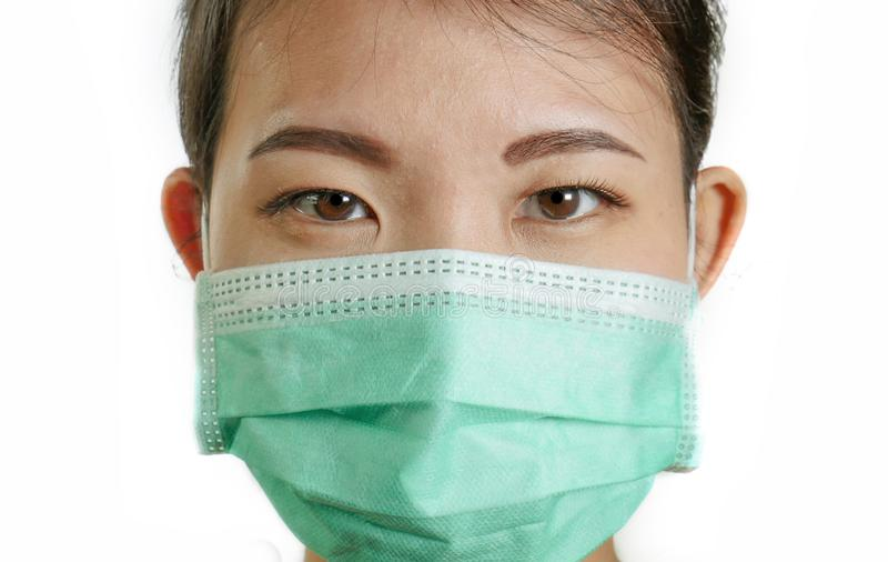 Close up portrait of young beautiful and attractive Asian Korean woman wearing blue protective face mask looking to the camera royalty free stock photo