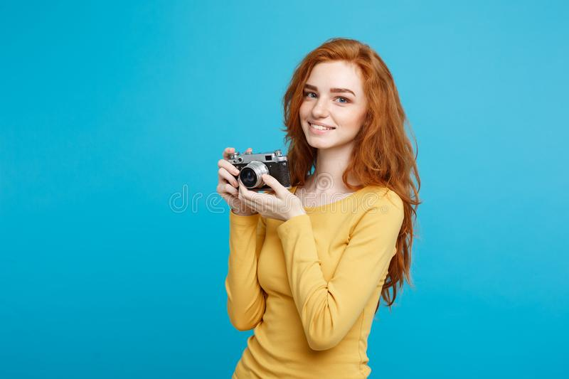 Close up Portrait young beautiful attractive ginger girl happy smiling with vintage camera and ready to travel. Blue stock photo