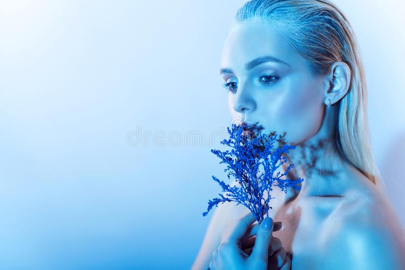 Close up portrait of young beautiful blond model with nude make up, slicked back hair holding a branch of blue flowers royalty free stock image