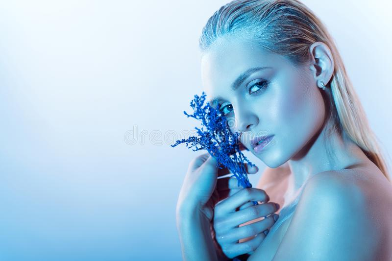 Close up portrait of young beautiful blond model with nude make up, slicked back hair and naked shoulders holding blue flowers royalty free stock photography