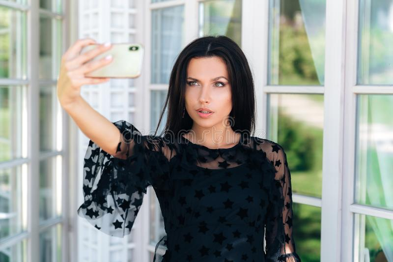 Close-up portrait of a young beautiful brunette girl holding her own mart in her hand, making selfie on the phone royalty free stock photos