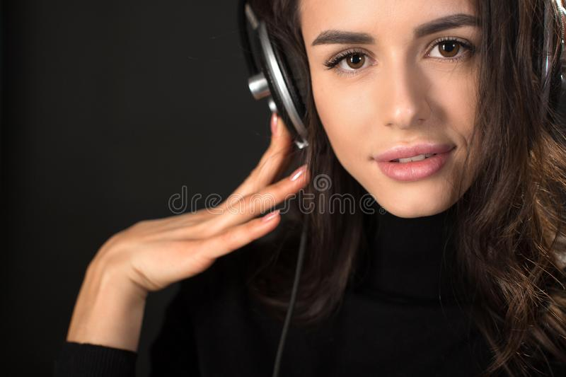 Close-up portrait of young beautiful brunette woman listening to music and holding headphones over dark grey background stock images