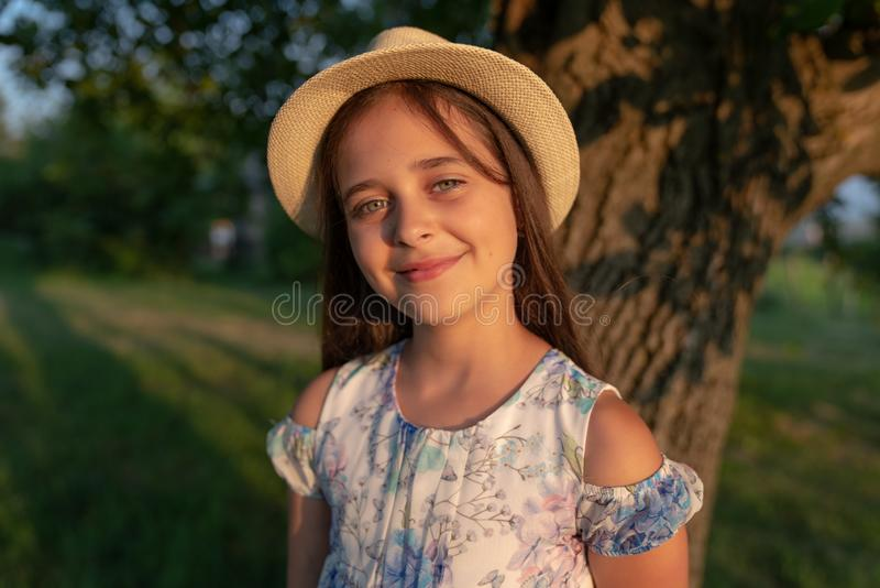 Close up portrait of young beautiful girl with healthy natural skin wearing white hat smiling and looking at the camera stock photo