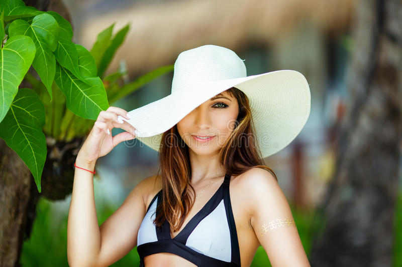 Close-up portrait young beautiful girl in a straw hat on the beach of a tropical island. Summer vacation concept. royalty free stock images