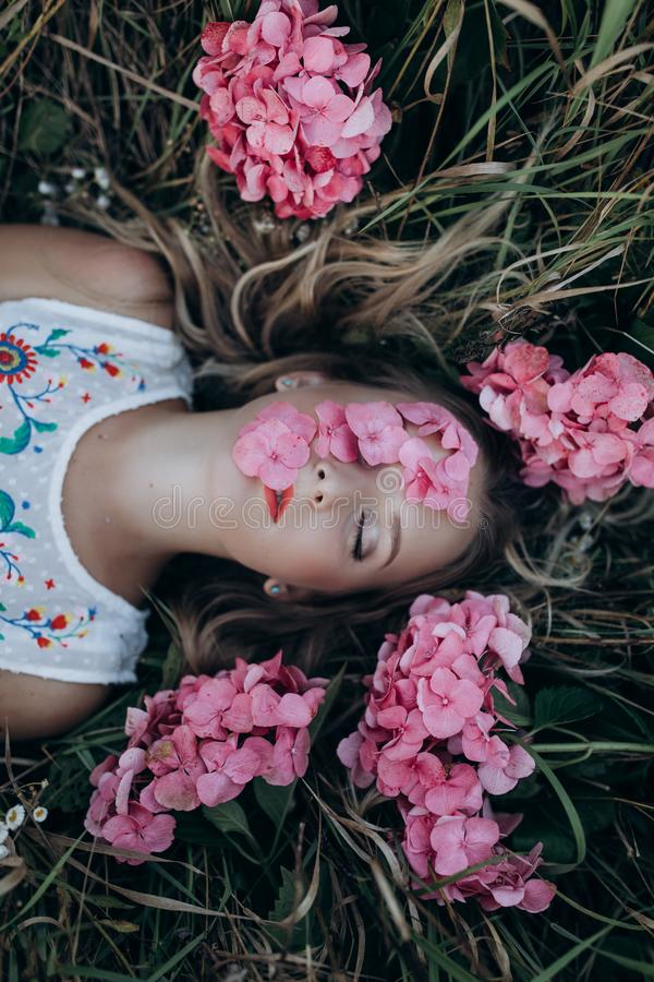 Close up portrait of young beautiful girl woman lying on grass with rose small flowers around her head stock photos