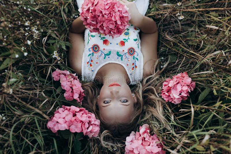 Close up portrait of young beautiful girl woman lying on grass with rose small flowers around her head royalty free stock images