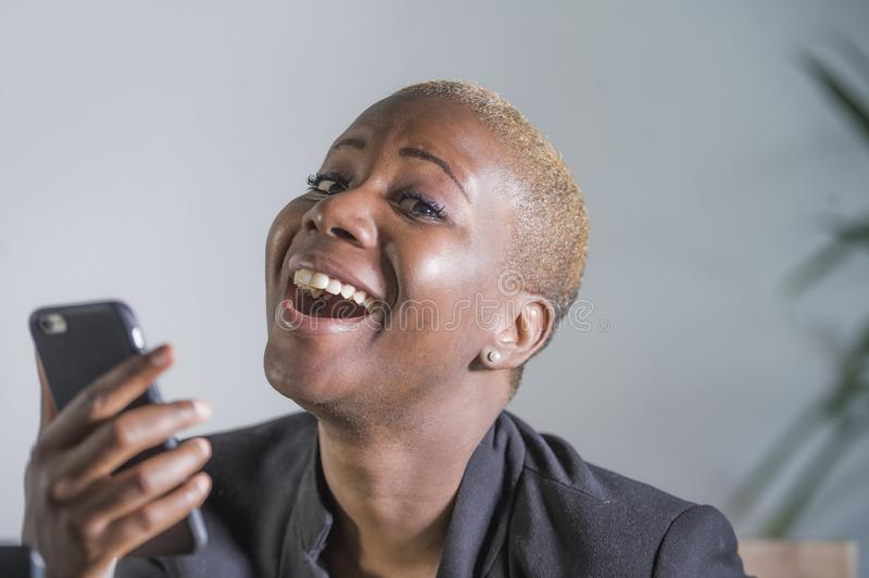 Close up portrait of young beautiful and happy trendy black afro american woman holding and using mobile phone isolated on grey ba stock image