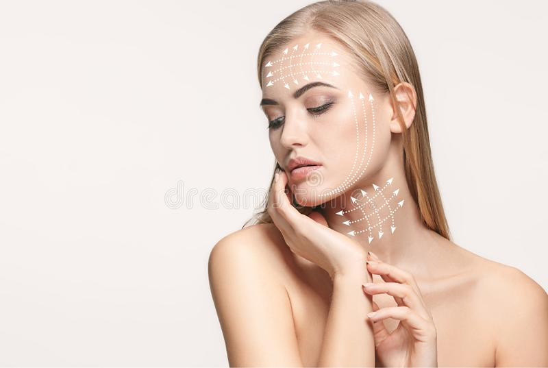 Close-up portrait of young, beautiful and healthy woman with arrows on her face. The spa, surgery, face lifting and skin care concept stock photography