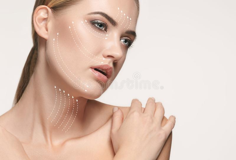 Close-up portrait of young, beautiful and healthy woman with arrows on her face. The spa, surgery, face lifting and skin care concept stock images