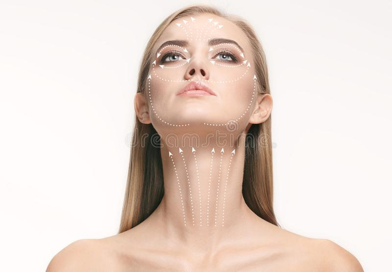 Close-up portrait of young, beautiful and healthy woman with arrows on her face. The spa, surgery, face lifting and skin care concept stock photos