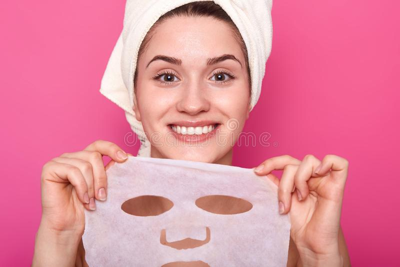 Close up portrait of young beautiful lady with perfect skin putting nourishing face mask, time to spa procedures, looks happy and. Relaxed, having white towel stock image