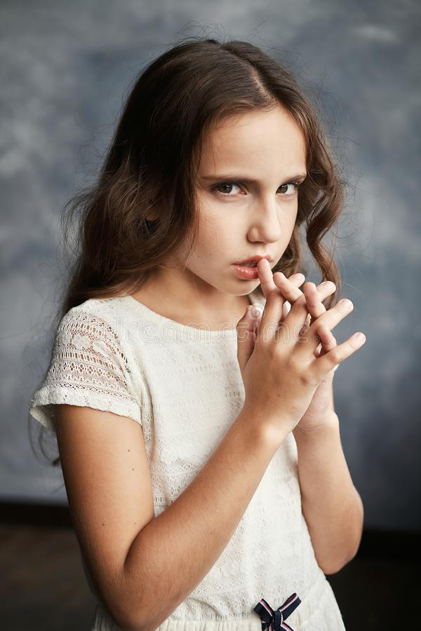 Close up portrait of young beautiful pensive girl in white shirt looking at camera. royalty free stock photography